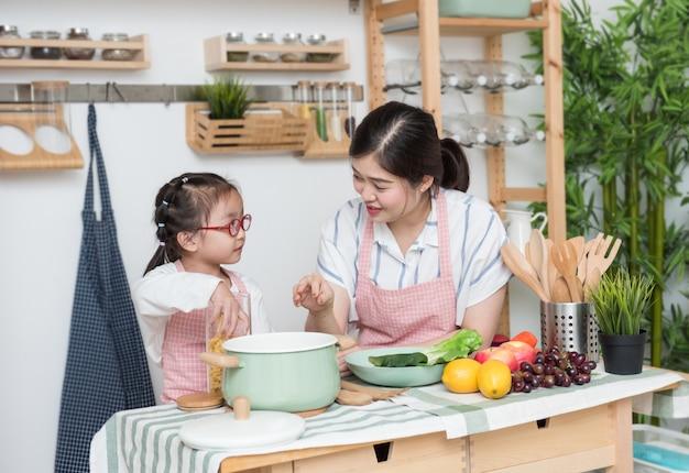 Madre asiática joven que enseña a cocinar para la hija o la hermana en la cocina.