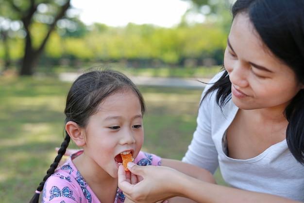 La madre asiática del primer alimenta un poco de fruta anaranjada para su hija en el jardín al aire libre.
