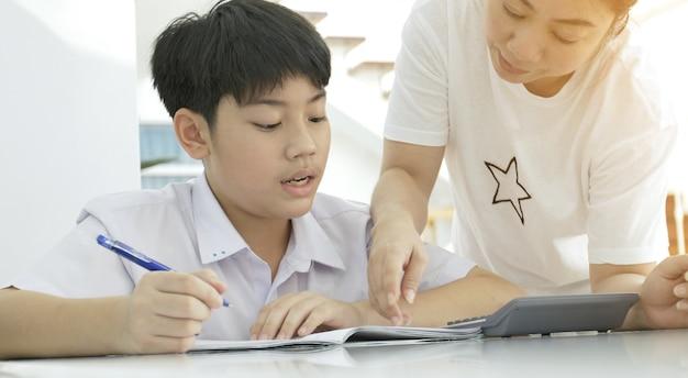 Madre asiática que ayuda a su hijo que hace la preparación en la tabla blanca.