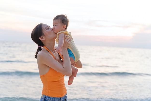 La madre asiática que se coloca en la playa sosteniendo a su bebé en dos brazos y criando al niño, besa al bebé.