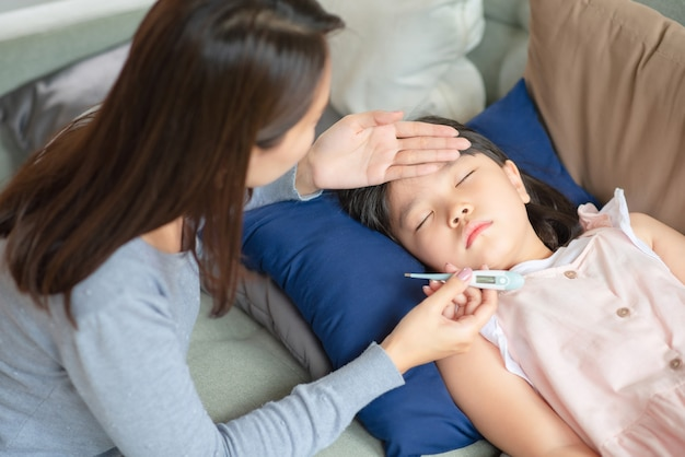 Madre asiática que controla la temperatura corporal de su hijo con un termómetro que tiene fiebre y enfermedad en casa.