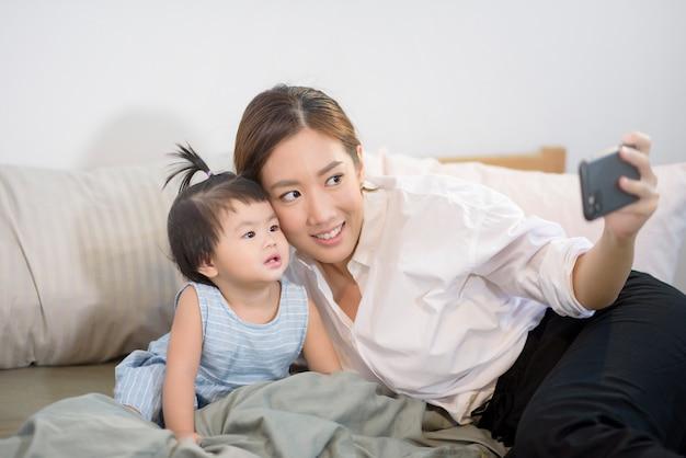 Madre asiática y su hija están haciendo selfie o videollamada al padre en la cama.