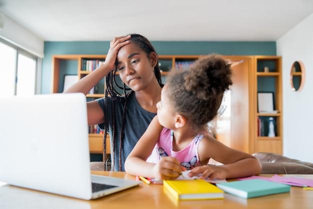 Madre ayudando y apoyando a su hija con la escuela en línea mientras se queda en casa. nuevo concepto de estilo de vida normal. concepto monoparental.