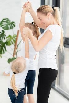 Madre ayudando a hijas a hacer ejercicio en casa