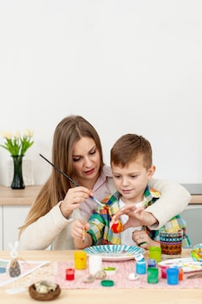 Madre ayudando a hijo a pintar huevos