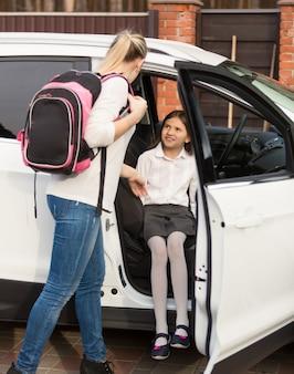 Madre ayudando a su hija a entrar en el coche después de las lecciones escolares