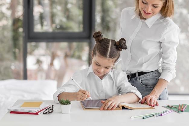 Madre ayudando a su hija a estudiar en casa