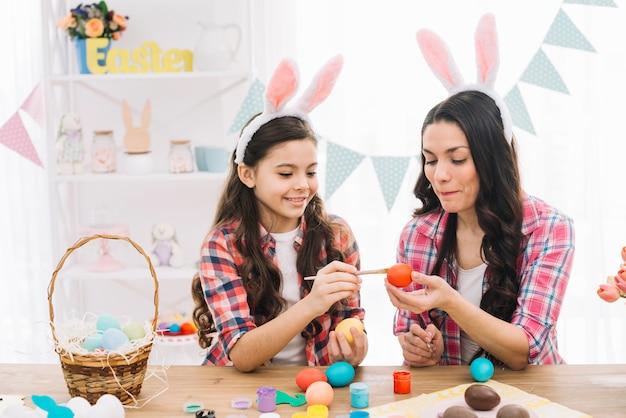 Madre ayudando a su hija a pintar el huevo de pascua en casa