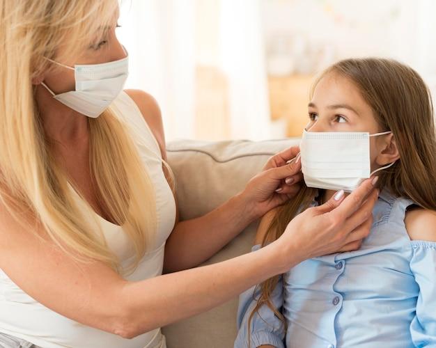 Madre ayudando a su hija a ponerse mascarilla médica en su rostro