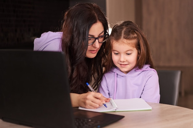 Madre ayudando a su hija durante sus deberes educación a distancia en línea en casa
