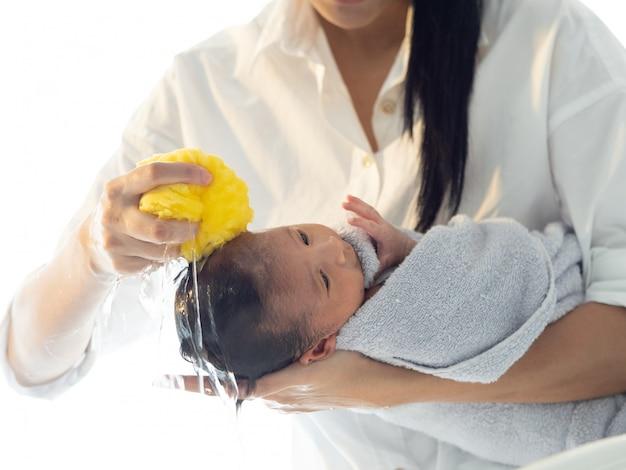 Madre baño bebé asiático bebé recién nacido en la bañera