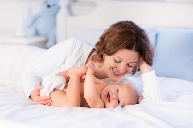 Madre y bebé en una cama blanca