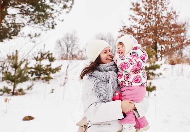 La madre y el bebé felices están sonriendo y abrazando