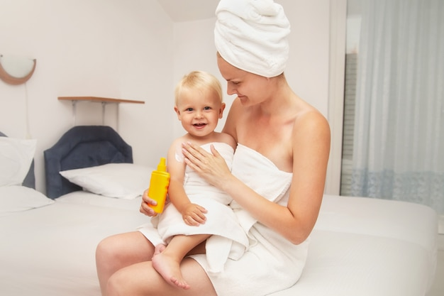 Madre y bebé feliz en toallas blancas después de bañarse, aplicar protector solar o crema solar.