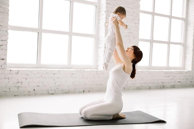 Una madre y un bebé haciendo gimnasia, ejercicios de yoga en el fondo de la pared blanca y grandes ventanales.
