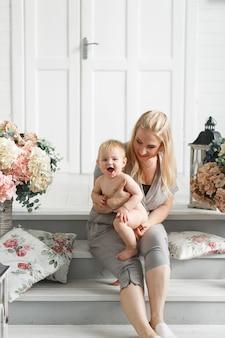 Madre con bebé juega en estudio decorado flores