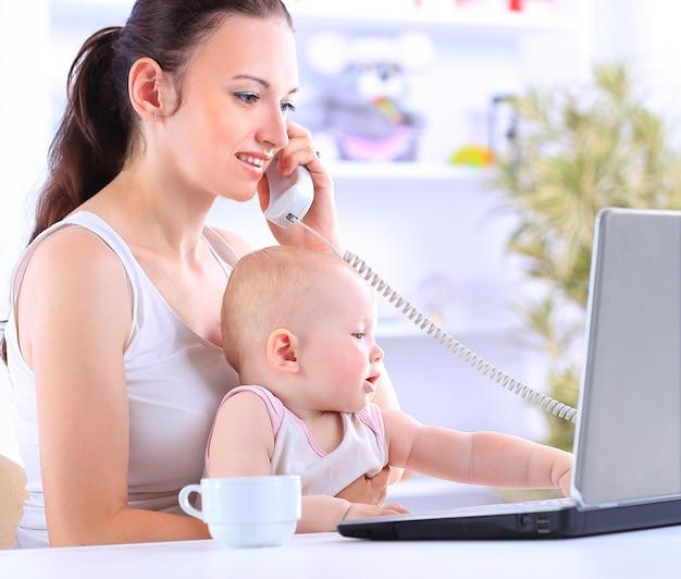 Madre y bebé en la oficina en casa con ordenador portátil y teléfono