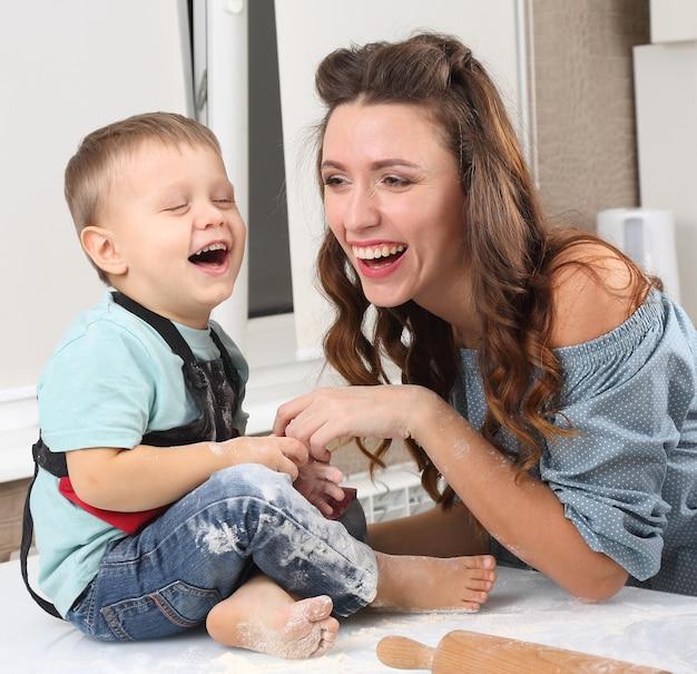 La madre y el bebé se ríen mientras preparan la masa en la cocina