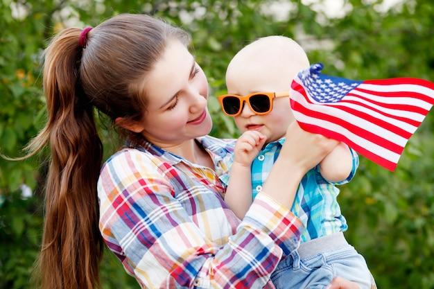 La madre y el bebé sostienen la bandera en la fiesta del 4 de julio