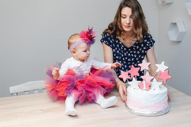 Madre y bebé con tarta de cumpleaños.