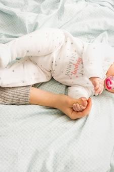 Madre y bebé tomados de la mano en cama ligera