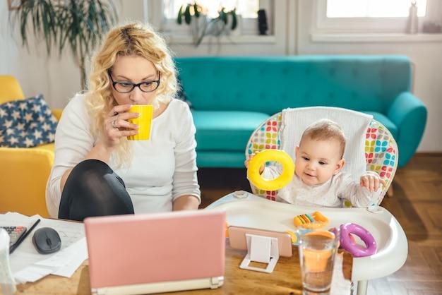 Madre con bebé trabajando en la oficina en casa y tomando café