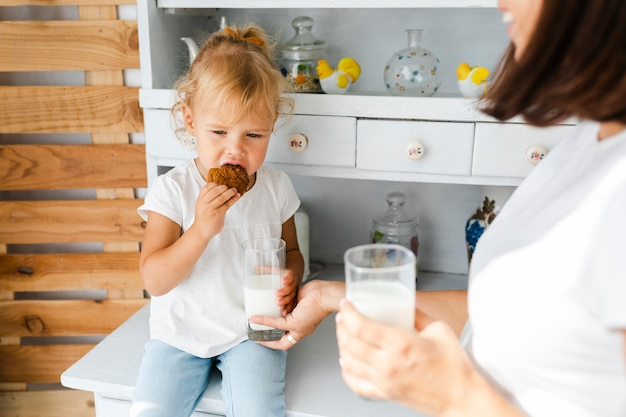 Madre bebiendo leche y su hija comiendo galletas