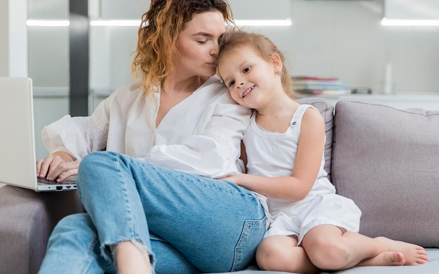 Madre besando a hija en la cabeza