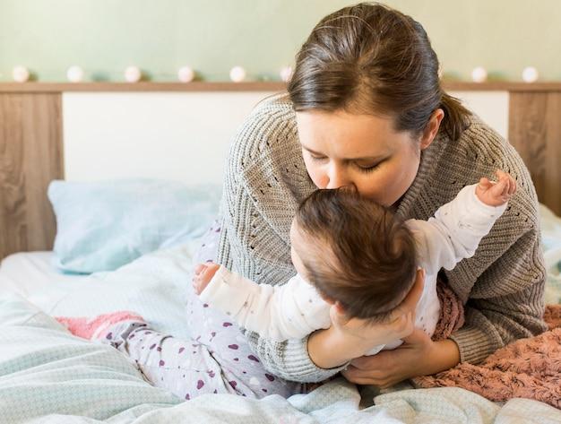 Madre besando lindo bebe en brazos