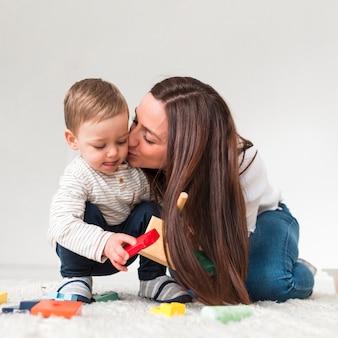Madre besando a un niño mientras juega