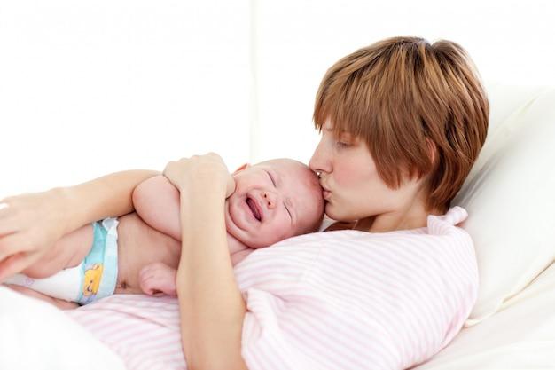 Madre besando a su bebé recién nacido