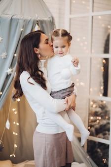 Madre besando a su hija en la mejilla. habitación decorada para navidad.