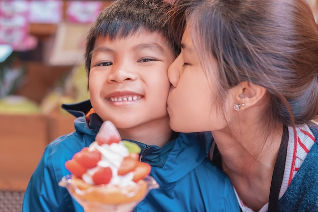 La madre está besando a su hijo sonriendo mientras come helado de postre de fresa en café japonés.