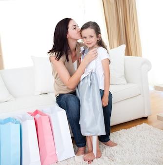 Madre besando a su niña después de ir de compras