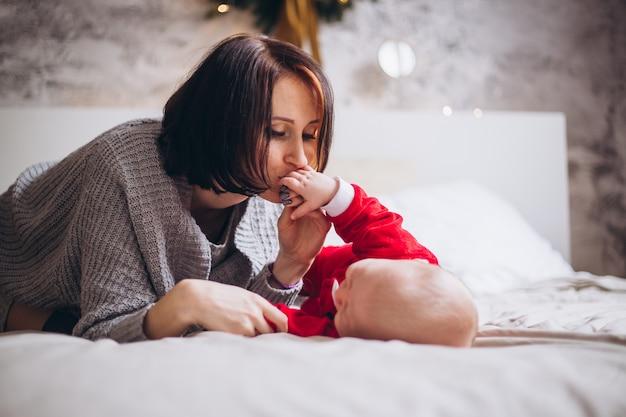 Madre besando a su pequeño bebé en casa en la cama