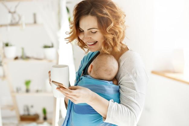 Madre bonita alegre con hijo dormido en honda del bebé, sosteniendo la taza de té en la mano y se ríe charlando con su mejor amiga en el teléfono inteligente en la habitación acogedora y luminosa.