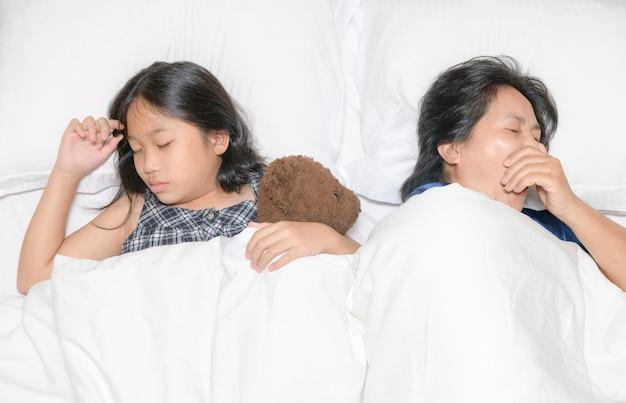 Madre bosteza y duerme con su hija en la cama, concepto de relax y cansancio.
