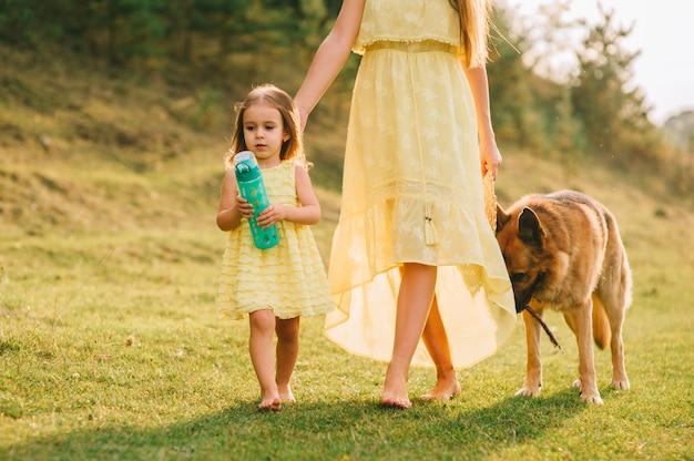 La madre camina con su hijita, y su perro.