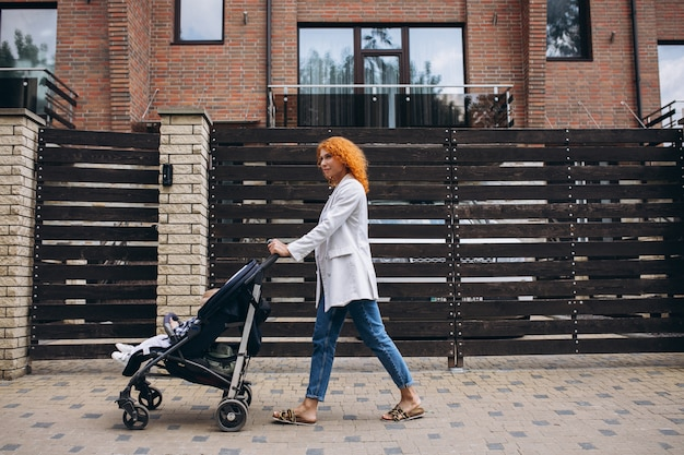 Madre caminando por la casa con su pequeño hijo en un cochecito de bebé