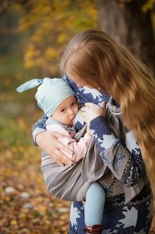 Madre caminando con el niño al aire libre, amamantando al bebé en cabestrillo