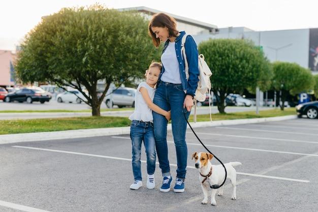 La madre cariñosa abraza a la pequeña hija, da un paseo al aire libre junto con su mascota favorita