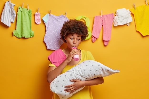Una madre cariñosa alimenta al bebé con un biberón de leche, chupa el pezón, sostiene en las manos al bebé envuelto en una manta y se ocupa de la nutrición del niño. recién nacido siendo alimentado por mamá. niñera ocupada posa con hijo pequeño