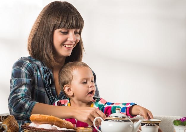 Madre cariñosa linda vierte té al pequeño hijo lindo