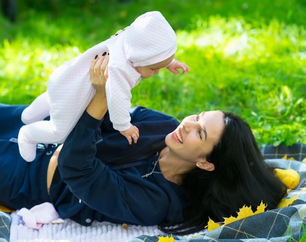 Madre cariñosa riendo mientras juega con su bebé levantándola en el aire mientras yace sobre una manta sobre la hierba verde en un parque en otoño