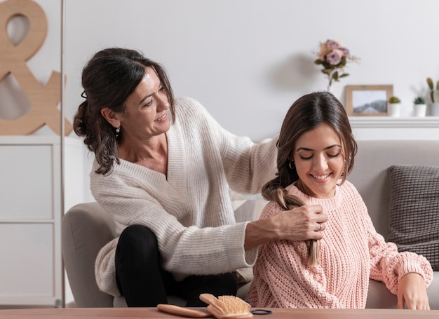 Madre en casa trenzando cabello niña