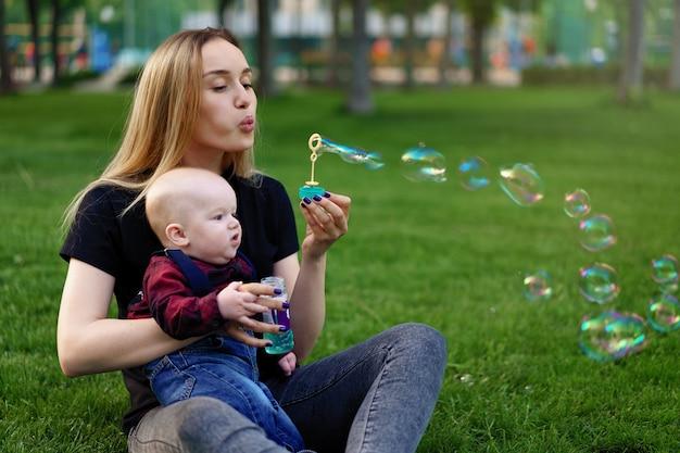 La madre caucásica joven infla burbujas de jabón con su pequeño hijo en un parque en un día de verano soleado.