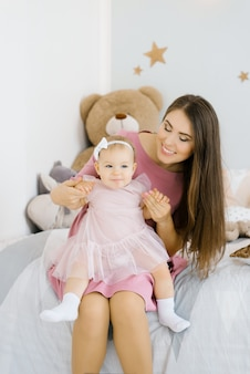 Una madre caucásica pone a su hija de un año en su regazo y la mira en la habitación de los niños en la casa y sonríe