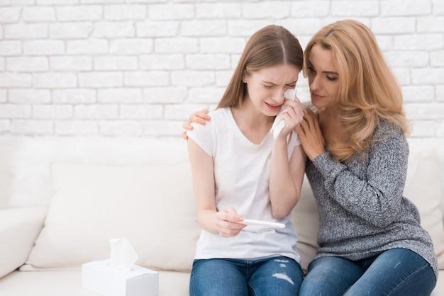 Madre cerca de hija molesta con la prueba de embarazo.