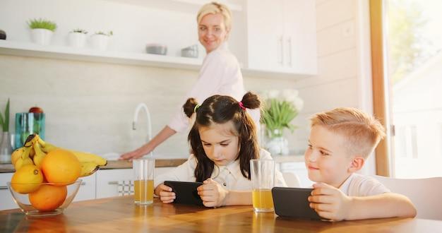 Madre cocina ans hermana y hermano viendo video en el teléfono móvil juntos.