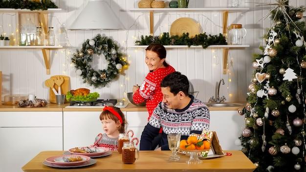 La madre cocina la cena festiva y el padre sonriente se sienta con una linda niña en la mesa de la cocina cerca del árbol de año nuevo decorado